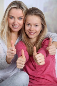 Portrait of mother and daughter with thumbs up